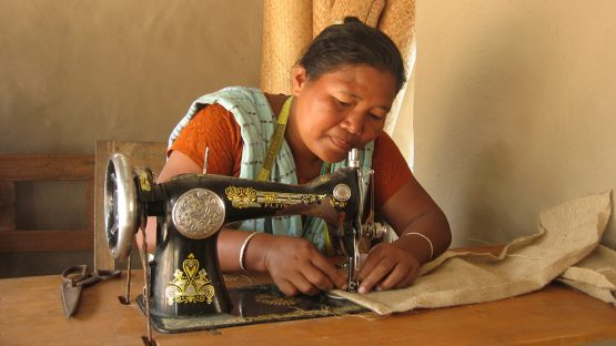 Pimola Nokrek sewing a jute bag