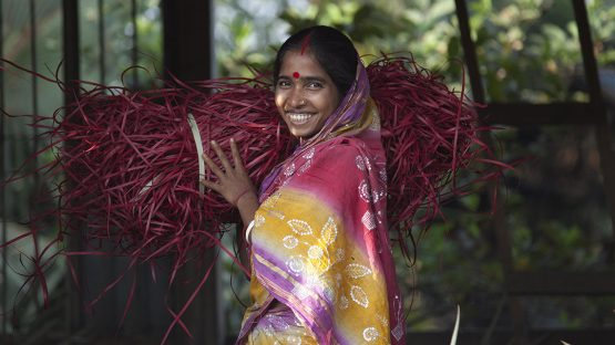 Gouri Adhikary carrying dyed palm leaves for basket weaving