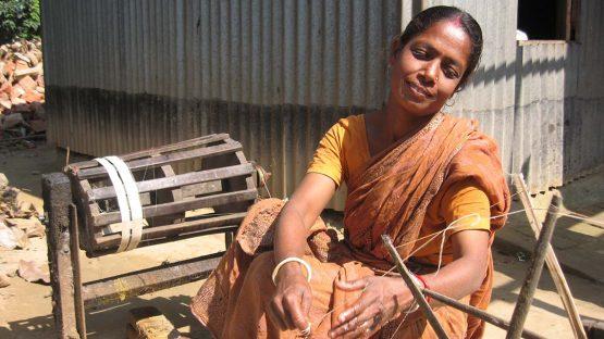 An artisan spinning silk prior to weaving