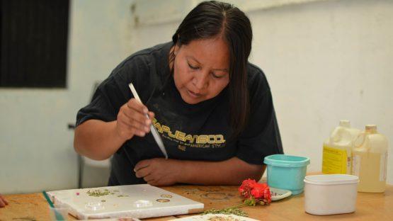 Marciela adding tiny flowers into resin jewellery
