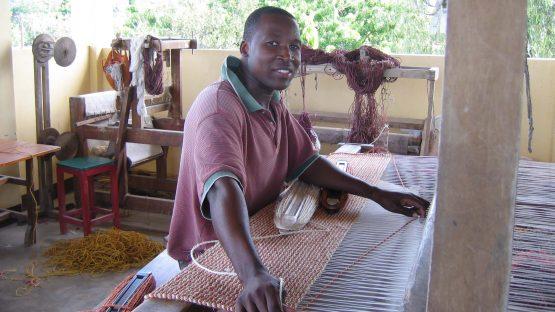 Michael Masanja weaving a rug