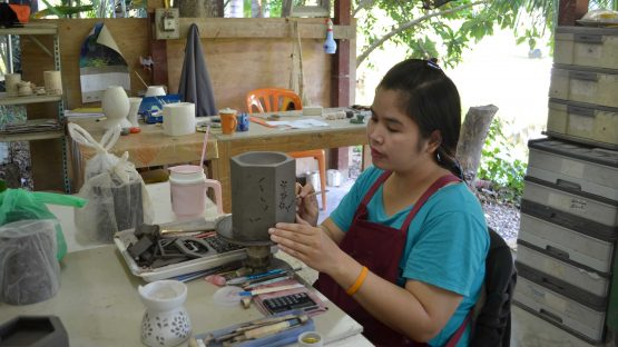 An artisan creating intricate patterns on an oil burner