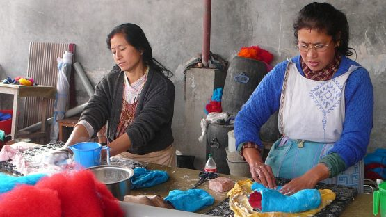 Two artisans felting wool