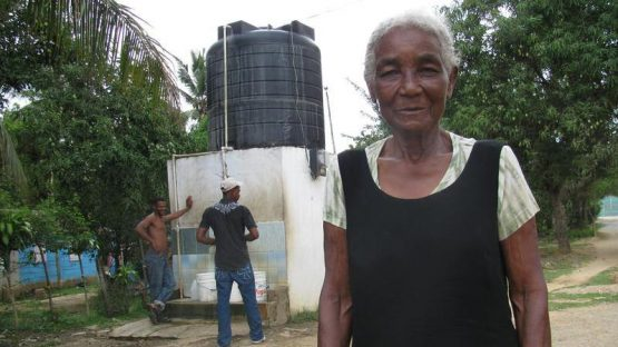 Maria Martinez Mansueta in front of a new community water supply funded by fair trade social premiums
