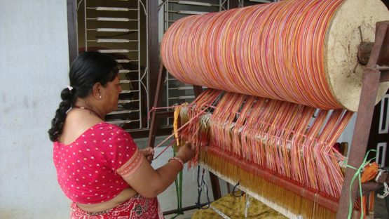 A artisan threading a loom