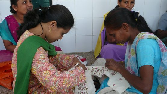 Two artisans working together on an embroidery piece
